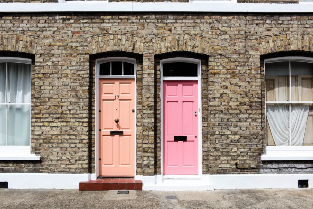 terrace houses one with an orange door and one with a pink door
