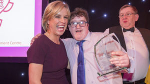 an award winner holds his award and smiles next to presenter Rona MacDougall