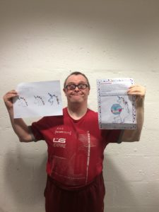 competition winner Stephen Dickson holds up his original unicorn drawing and the unicorn mascot design and smiles