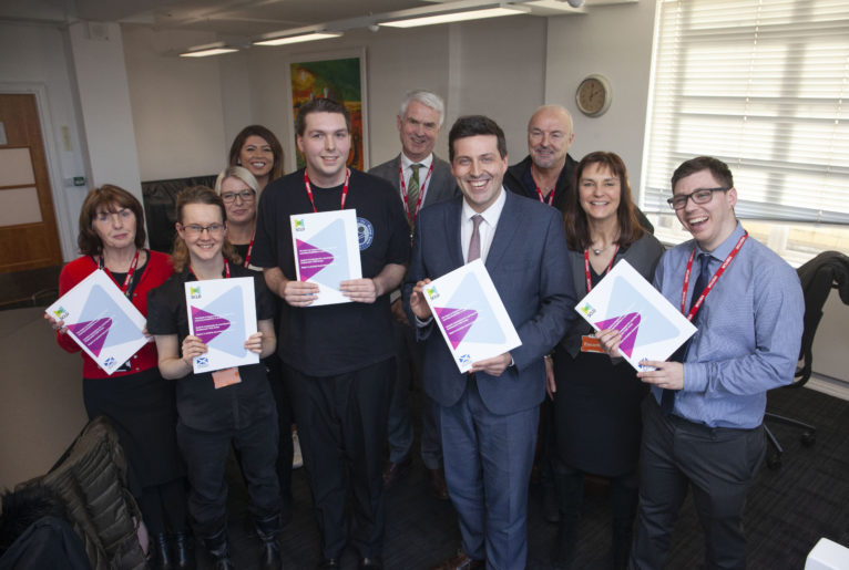 Minister for Business, Fair Work and Skills, Jamie Hepburn MSP stands front and centre holding a copy of the report, surrounded by Eddie, Kieran and Kirsty, their job coaches and SCLD staff, holding reports and smiling