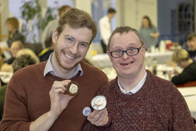 celebrity baker James Morton sits beside Stephen Dickson who designed the Learning Disability Week mascot, 'Uno the Unicorn', both holding cup cakes with Uno the Unicorn cake toppers on them.