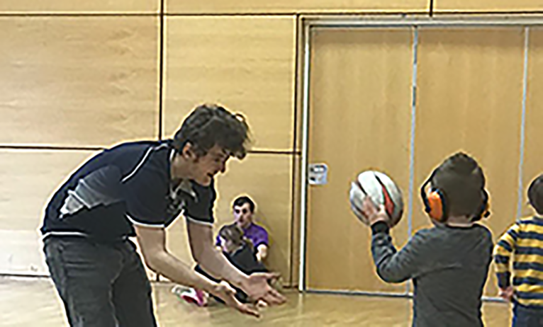 Stephen plays rugby with a child with learning disabilities in a sports hall
