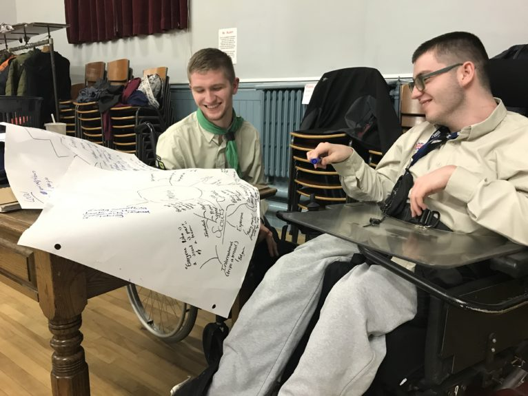 Michael and Ross sit in their scouting uniforms and plan out what community means to them on a sheet of A3 paper