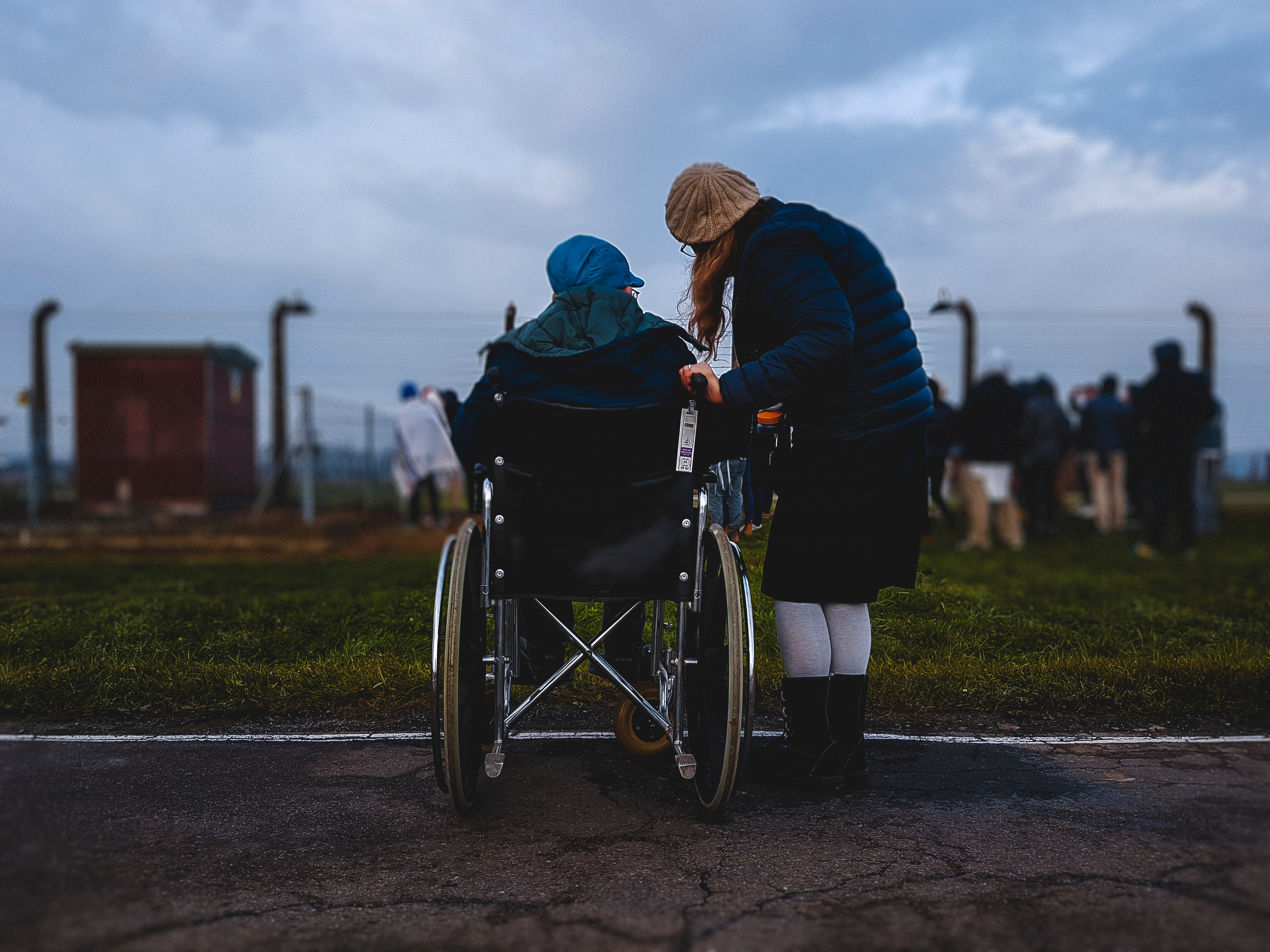 Person in a wheelchair sits looking out at field, beside them is a woman speaking to them.