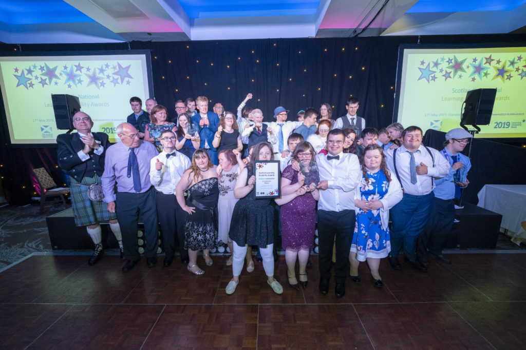 All the 2019 finalists smile and cheer whilst holding their awards on stage at the Learning Disability Awards 2019