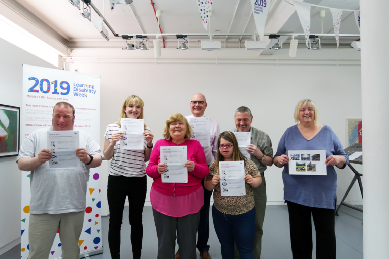 people stand smiling with copies of the 'How's Life?' survey at the survey launch event