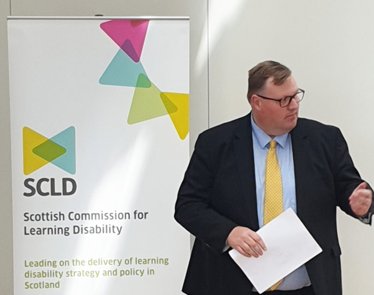 Councillor Currie stands in front of an SCLD banner to launch the local strategy guidance