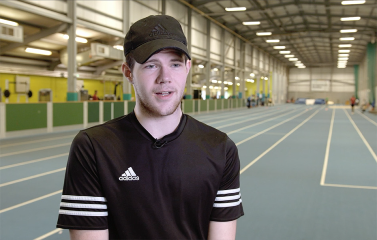 Award winner Lewis McDermid talks in front of an indoor athletics track