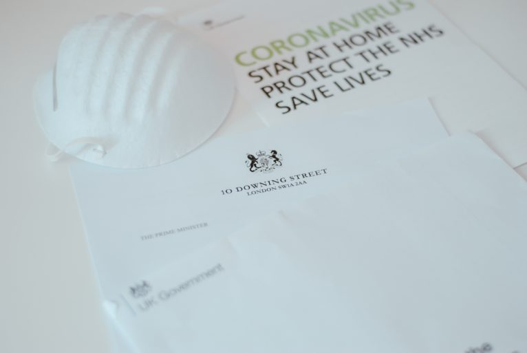 A face mask, NHS Coronavirus advice leaflet and a letter from Downing Street lie on a white table.