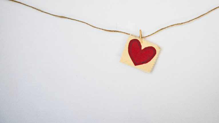 A picture of heart on a piece of string against a white wall. Photo credit: Debby Hudson on Unsplash.