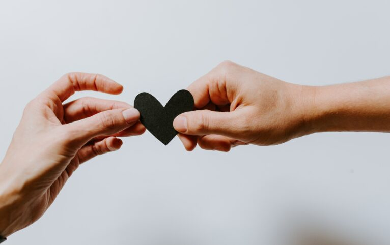 Two people hold a small black paper heart between their hands. Photo credit: Kelly Sikkema on Unsplash.