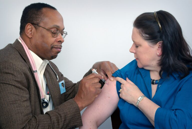 A doctor gives a woman a vaccination. Photo by CDC on Unsplash.